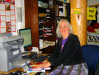 Image: White-haired woman sitting at the desk at the UNM-Taos Library